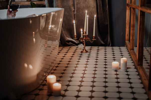lighted candles on table near glass cup